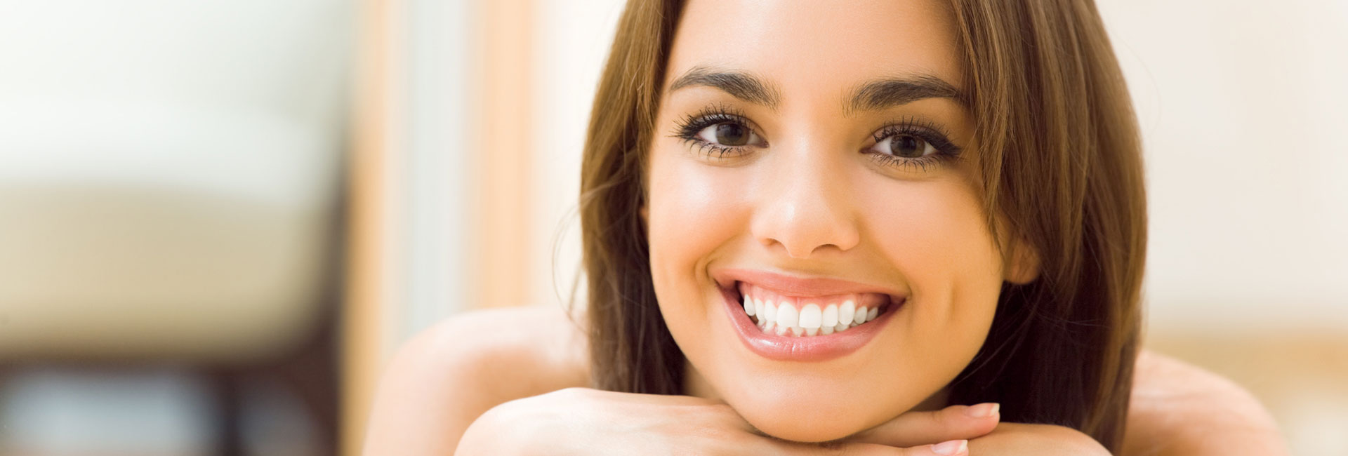 Young smiling woman with dental crowns